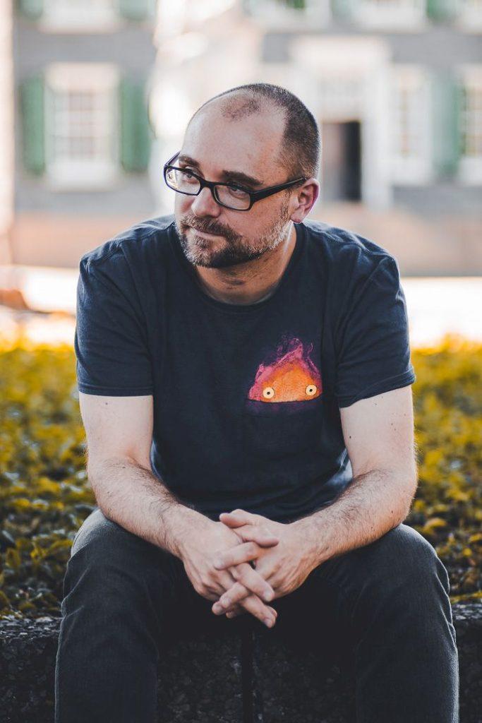 Ein Mann mit Bart und Brille sitzt vor einem nur verschwommen wahrnehmbaren Haus.